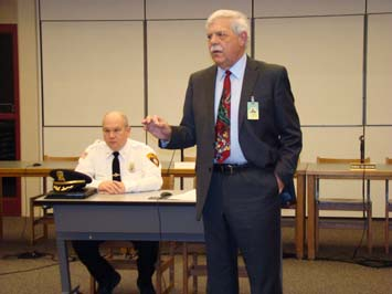Two Local Bullies: Darlington (seated, as usual) and McCartney, anti-military biased school superintendent)